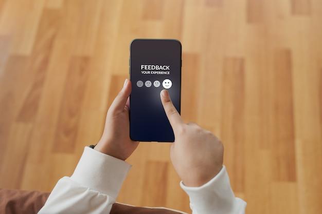 Hand selecteer glimlach pictogram op mobiele telefoon
