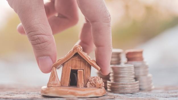 Hand selecteer munten stapel thuis model op houten tafel