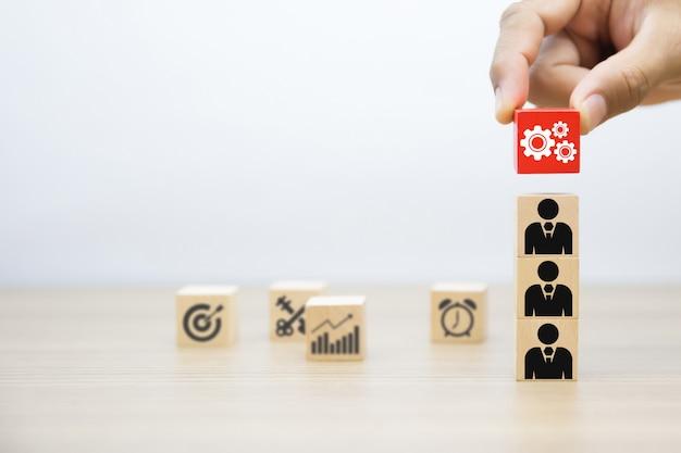 Hand selecteer versnelling symbool op houten speelgoed blok.