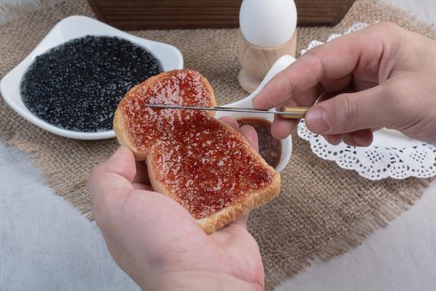 Hand slathers jam op brood met mes.