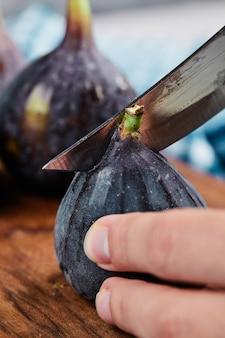 Hand snijden een vijg op houten snijplank.