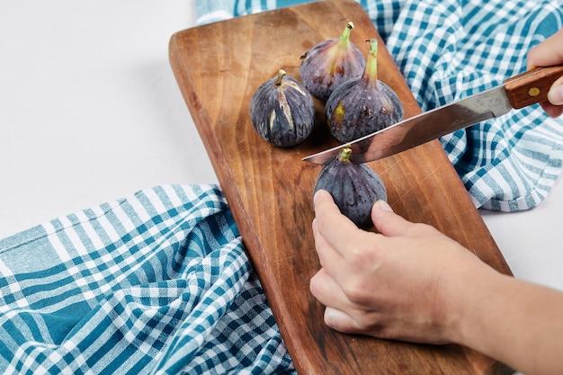 Hand snijden van een vijg op houten snijplank met een blauw tafelkleed.