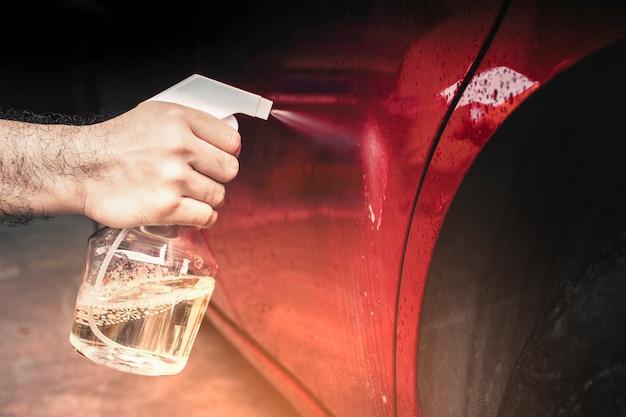Hand sproeide chemische vloeistof op de carrosserie met een watersproeifles van dichtbij