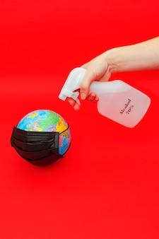 Hand sproeien van alcohol op earth globe-model met zwart chirurgisch masker geïsoleerd op rode achtergrond