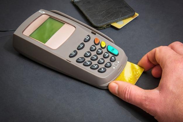 Hand steekt bankkaart in de geldterminal voor betaling op kantoor zwarte tafel, bovenaanzicht