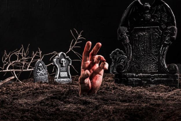 Hand steekt graf uit op donkere begraafplaats