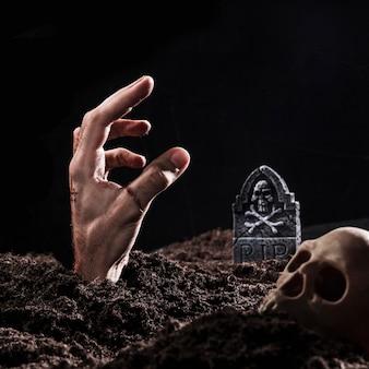 Hand steekt uit de grond in de buurt van grafsteen