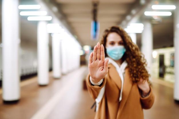Hand stopbord. vrouw met een steriel medisch masker op haar gezicht, toont stophandengebaar voor stop uitbraak van coronavirus op metrostation.