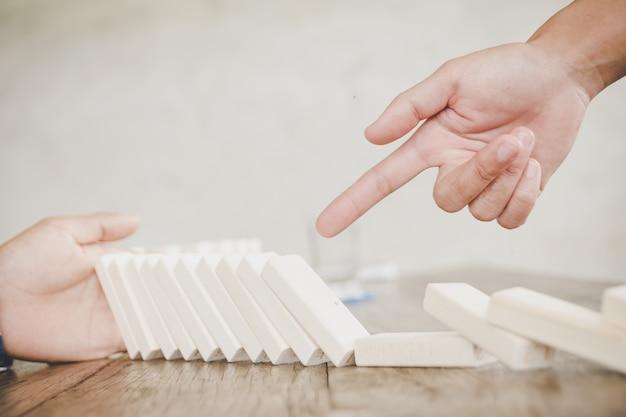 Hand stoppen domino-effect van houten blokken voor concept over bedrijf en verantwoording.