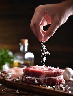 Hand strooien van zout op vers rauw rundvlees op een snijplank