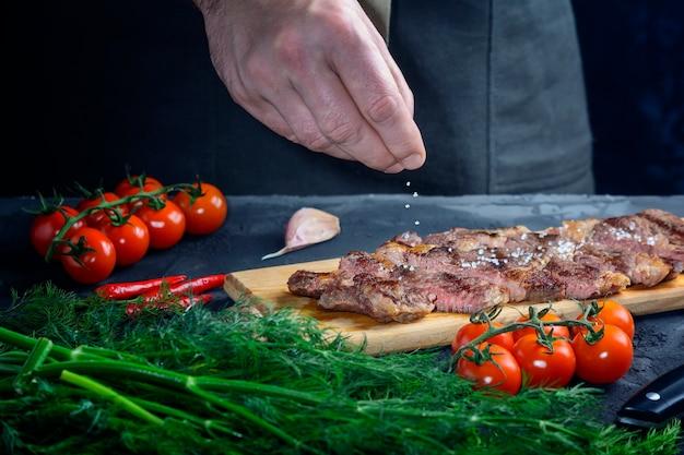 Hand strooit zout op een biefstuk