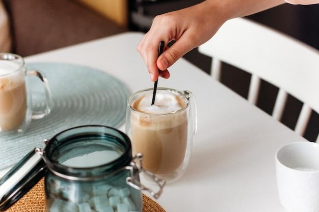 Hand suiker roeren met een lepel in een mok met koffie op witte tafel