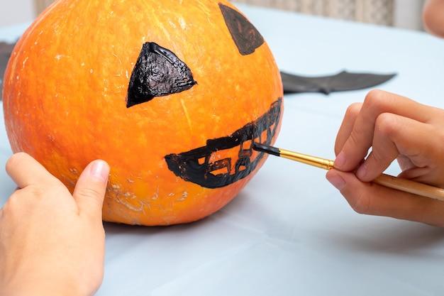 Hand tekenen van een eng gezicht op een oranje pompoen met een borstel om een halloween jack lantern, close-up te maken. achtergrond voor halloween-feest en familielevensstijl