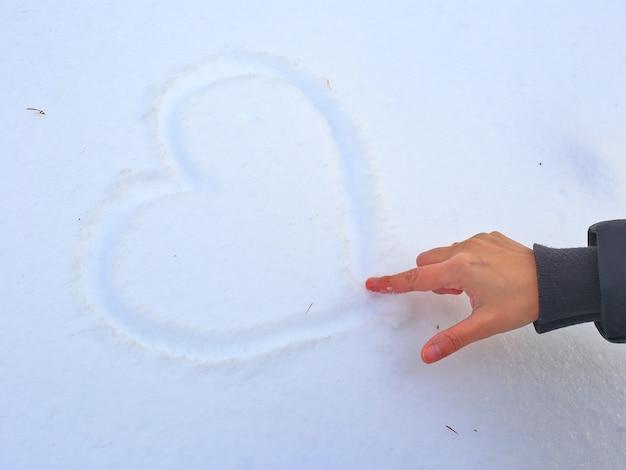 Hand tekenen van een hart in de sneeuw