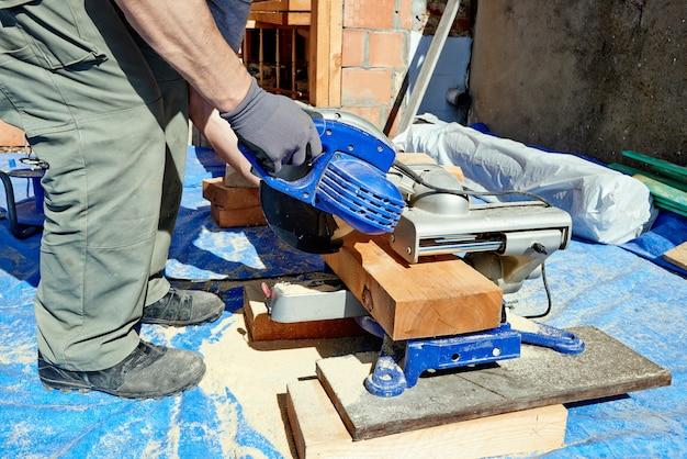 Hand timmerman die elektrische zaag gebruikt