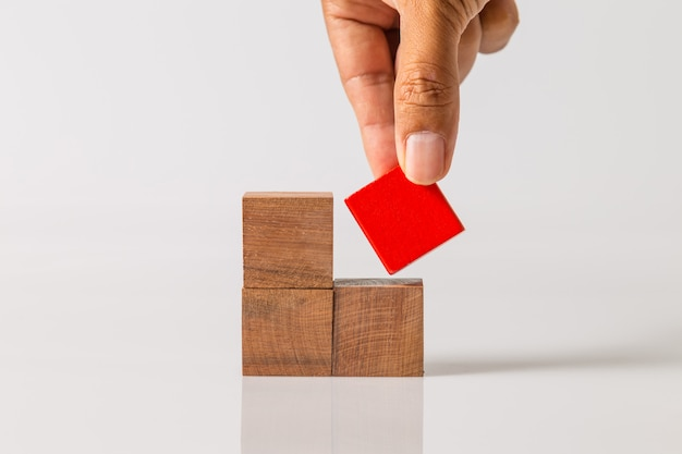 Hand toevoegen van het laatste ontbrekende houten blok op zijn plaats. succes bedrijfsconcept.