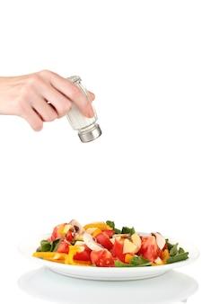 Hand toevoegen van zout met behulp van zout shaker geïsoleerd op wit