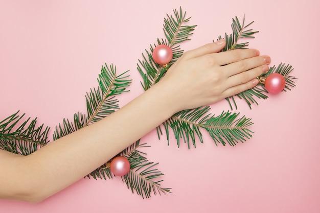 Hand tot op de fir-tak met roze ballen
