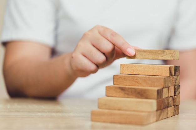 Hand trekken of plaatsen van houtblok op de toren, plan en strategie in het bedrijfsleven