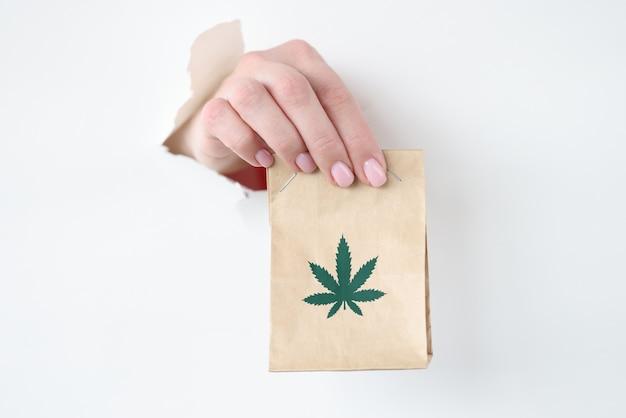 Hand trekken papieren zak marihuana uit gescheurd papier