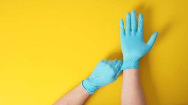 Hand trekt blauwe latexhandschoenen op gele achtergrond.