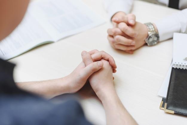 Hand, twee mannen op een bureau. onderhandelen over zaken. communicatie en onderhandelingen tussen twee zakenlieden