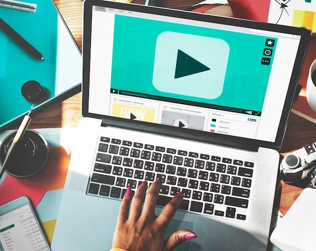 Hand typen op laptop met afspeelknop op scherm