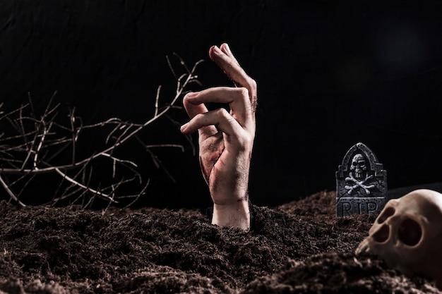 Hand uit de grond steken in de buurt van de schedel