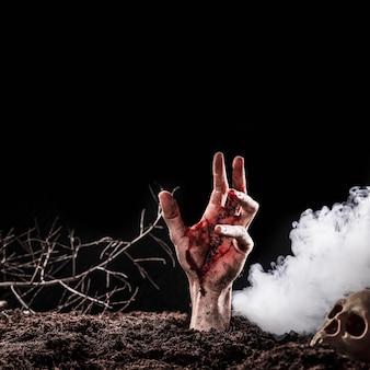 Hand uit de grond steken in de buurt van zware mist