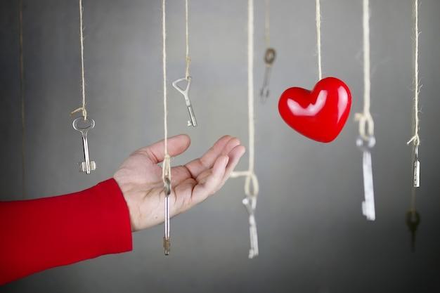 Hand uitrekken voor een van de vele oude vintage sleutels die aan draden hangen