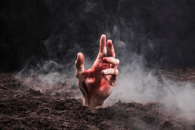 Hand uitsteekt van de bodem