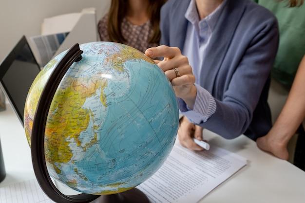 Hand van aardrijkskundeleraar wijzend op continent op wereldbol