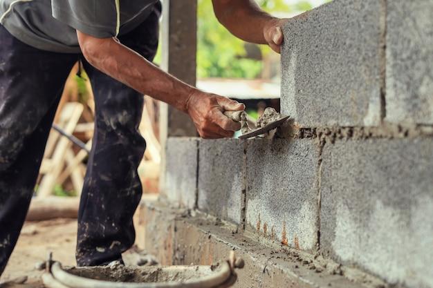Hand van arbeider het pleisteren cement op bakstenen muur bij bouwwerf
