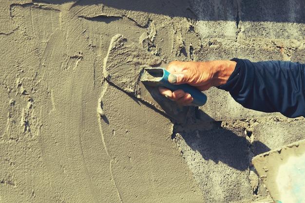 Hand van arbeider het pleisteren cement op muur