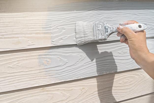 Hand van arbeider het schilderen op houten muur nieuw huis bij bouwwerf.