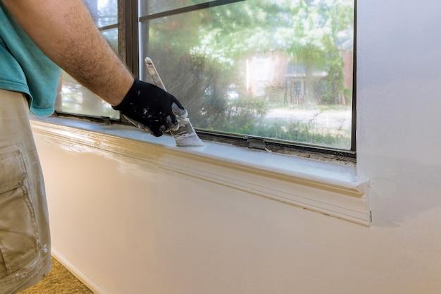 Hand van arbeider met handschoenen in de lijst van het schilderen van de vensterlijst