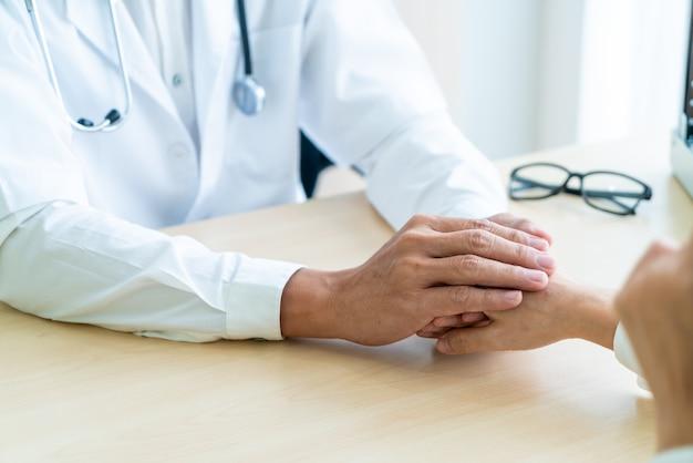 Hand van arts geruststellend haar vrouwelijke patiënt
