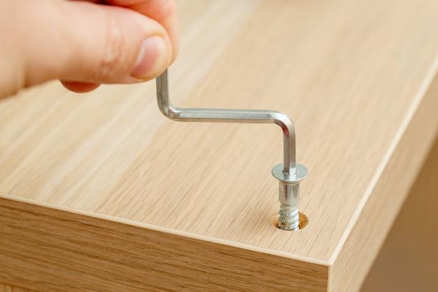 Hand van assemblagewerker met zeshoekige sleutel schroeven meubelschroef