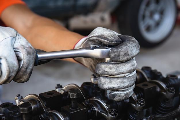 Hand van automonteur die een motor aanpast met dopsleutel, autoreparatieservice in werkplaats
