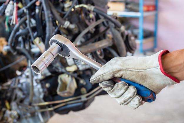 Hand van automonteur met dopsleutel, autoreparatieservice in de werkplaats