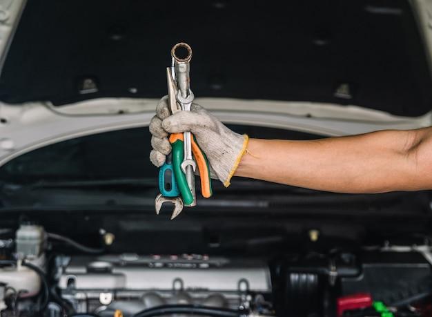 Hand van automonteur met moersleutel automonteur reparatieonderhoud en auto-inspectie