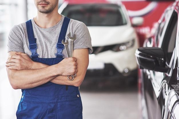 Hand van automonteur met moersleutel.