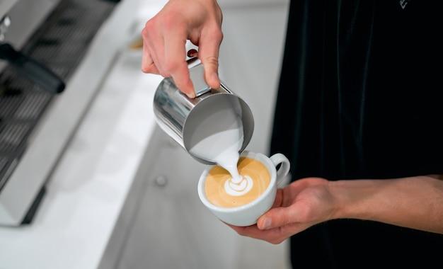 Hand van barista die latte of cappuccino koffie gietende melk maakt die latte art.