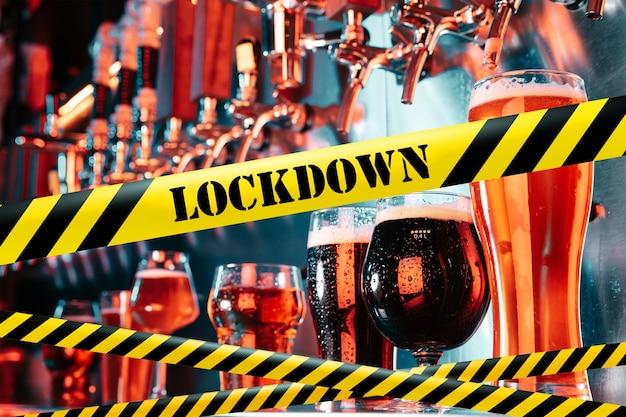 Hand van barman die een biertje in de kraan giet met begrenzingsbanden lockdown coronavirus