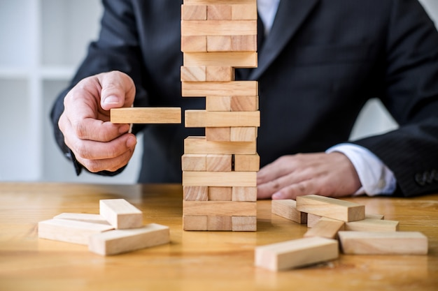 Hand van bedrijfsmensen die houtsnede op de toren plaatsen en trekken