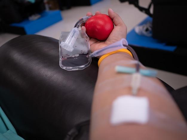 Hand van bloeddonorkogel tijdens procedure van het verzamelen van aderlijk bloed