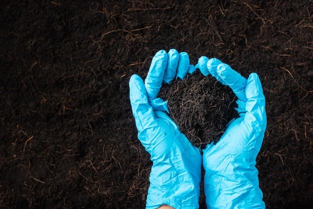 Hand van boer of onderzoeker vrouw draagt ?? handschoenen met overvloed aan vruchtbare zwarte grond