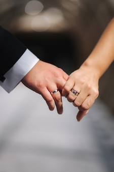 Hand van bruid en bruidegom houden elkaar vast. detailopname.