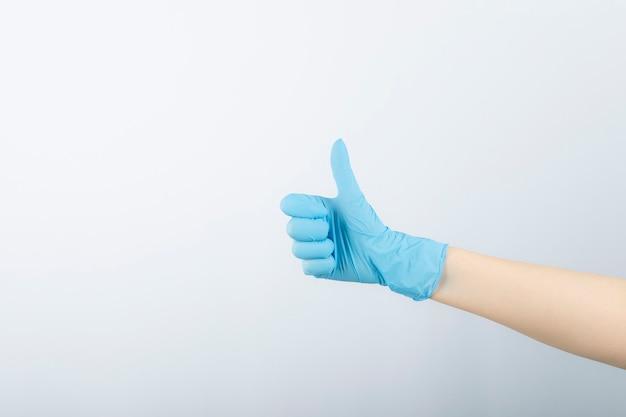 Hand van chirurg in blauwe medische handschoen die een duim toont.