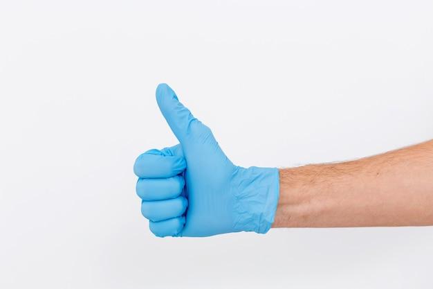 Hand van chirurg in blauwe medische handschoen die ok teken toont, geïsoleerd op een witte achtergrond